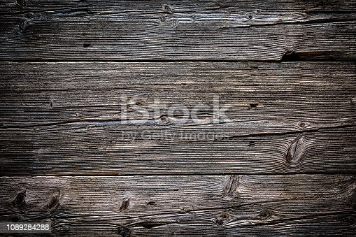 Front view of an old weathered wooden plank with several horizontal stripes. Predominant color is brown. DSRL studio photo taken with Canon EOS 5D Mk II and Canon EF 100mm f/2.8L Macro IS USM.