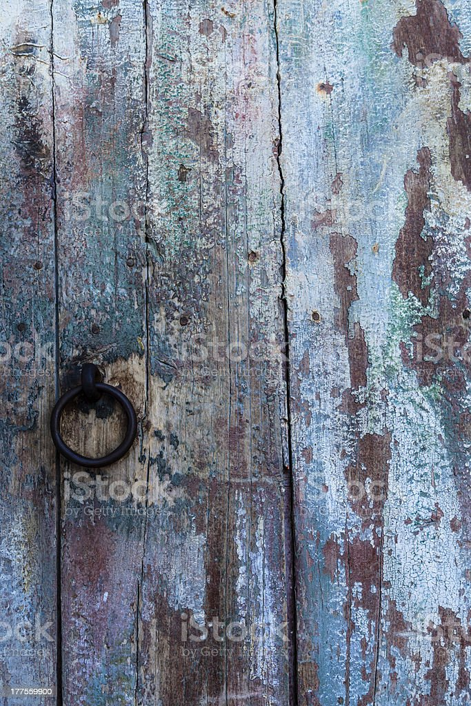 Old Wooden Planks Door with ruined paintings and rusty ring royalty-free stock photo