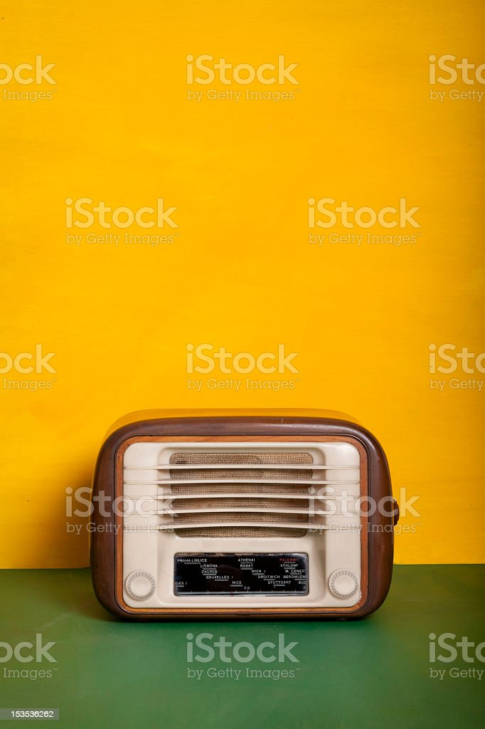 Old wooden radio equipment on green table and yelllow background stock photo