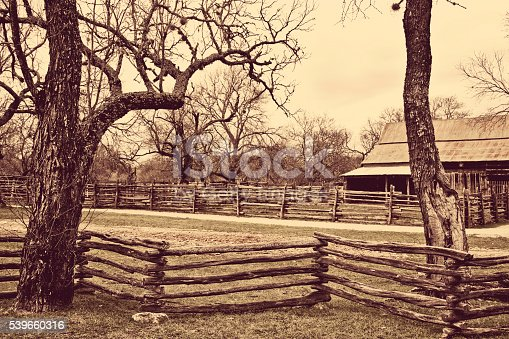 Rustic, weathered wooden fence provides boundary on ranch pasture.  Barn in background.  Sepia tones.  No people.