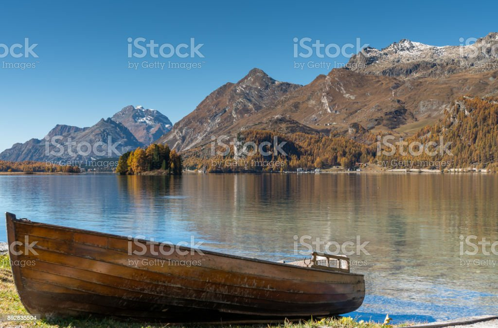 old wooden rowboat on the shores of a lake in the Swiss Alps stock photo