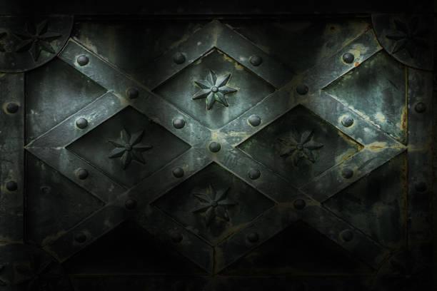 Alte, rostige mittelalterliche Holzmauer mit Rhombus-Muster mit Sternen und Nieten, die von drei Scheinwerfern als Hintergrund beleuchtet werden. – Foto