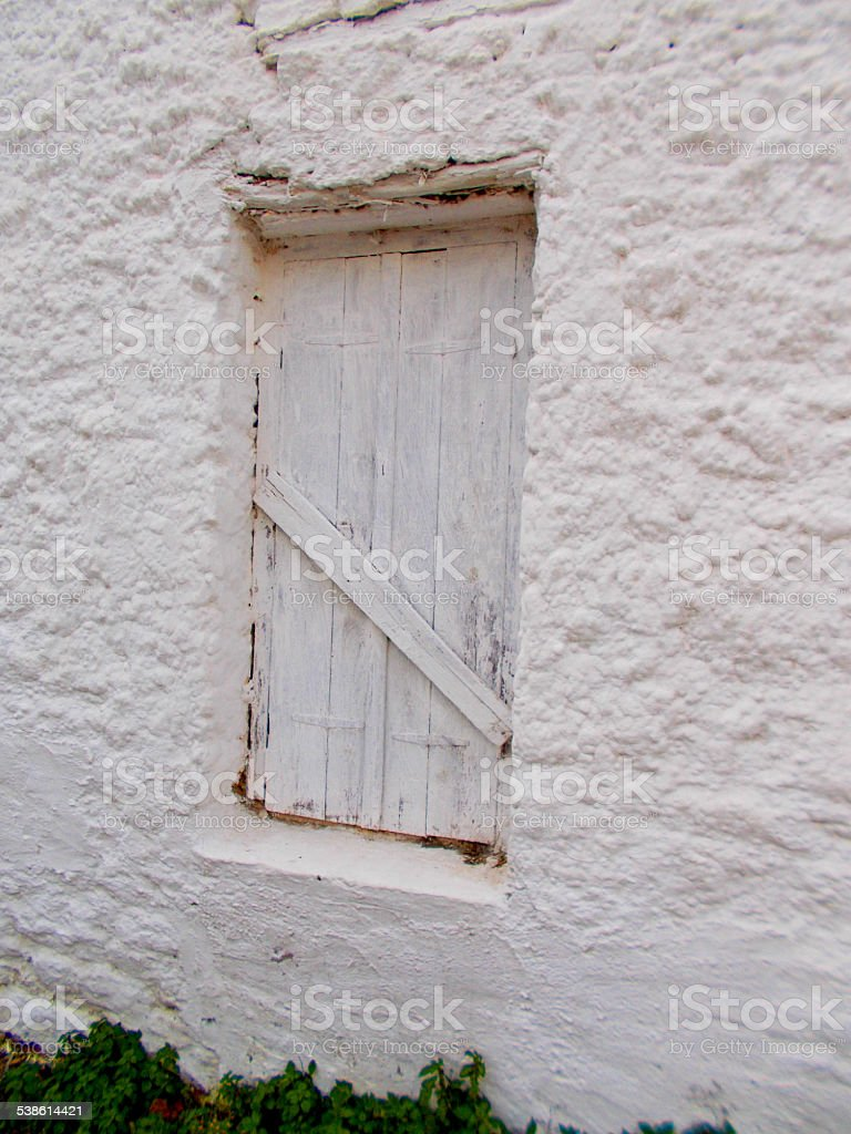 Old wooden shutter on a whitewashed wall stock photo