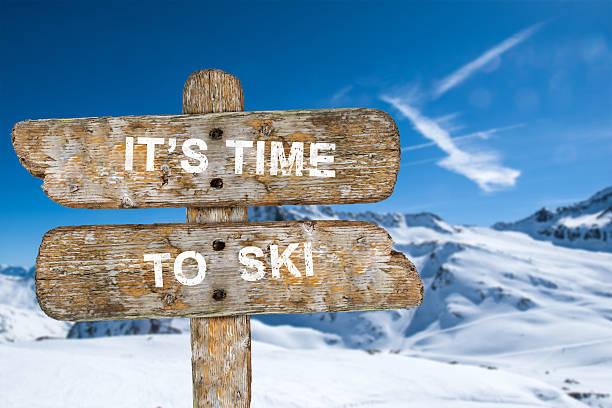 old wooden signpost with the inscription. it's time to ski. - sprüche zeit stock-fotos und bilder