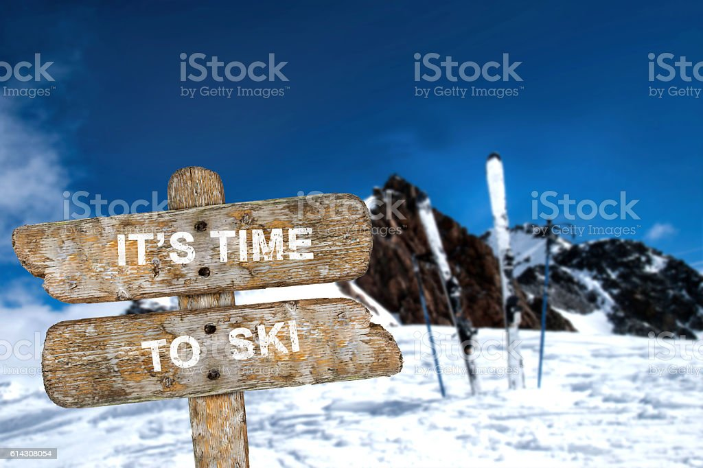 Old wooden signpost with the inscription. It's time to ski. stock photo