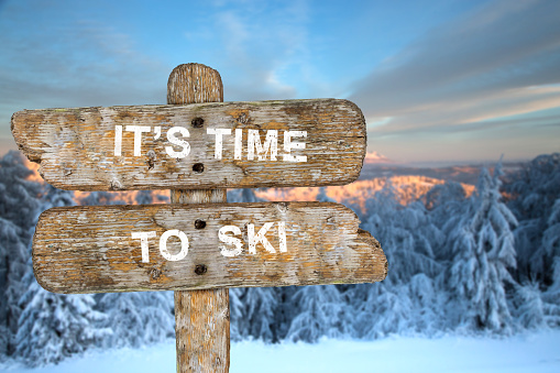 Old wooden signpost with the inscription. It's time to ski.