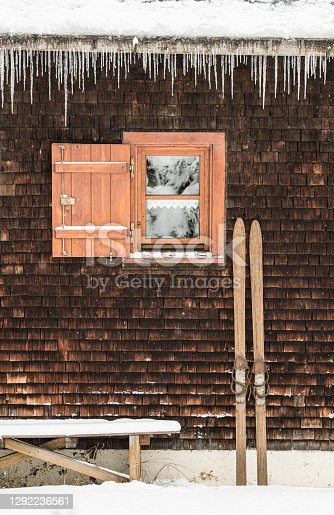 Old wooden ski leaning at the shingled wall of a cabin. There are icicles at the roof and snow on the ground.