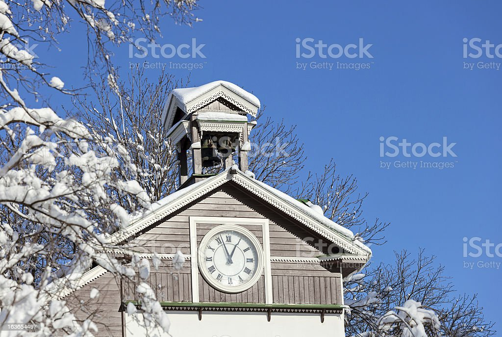 Old wooden snow covered chapel with clock royalty-free stock photo