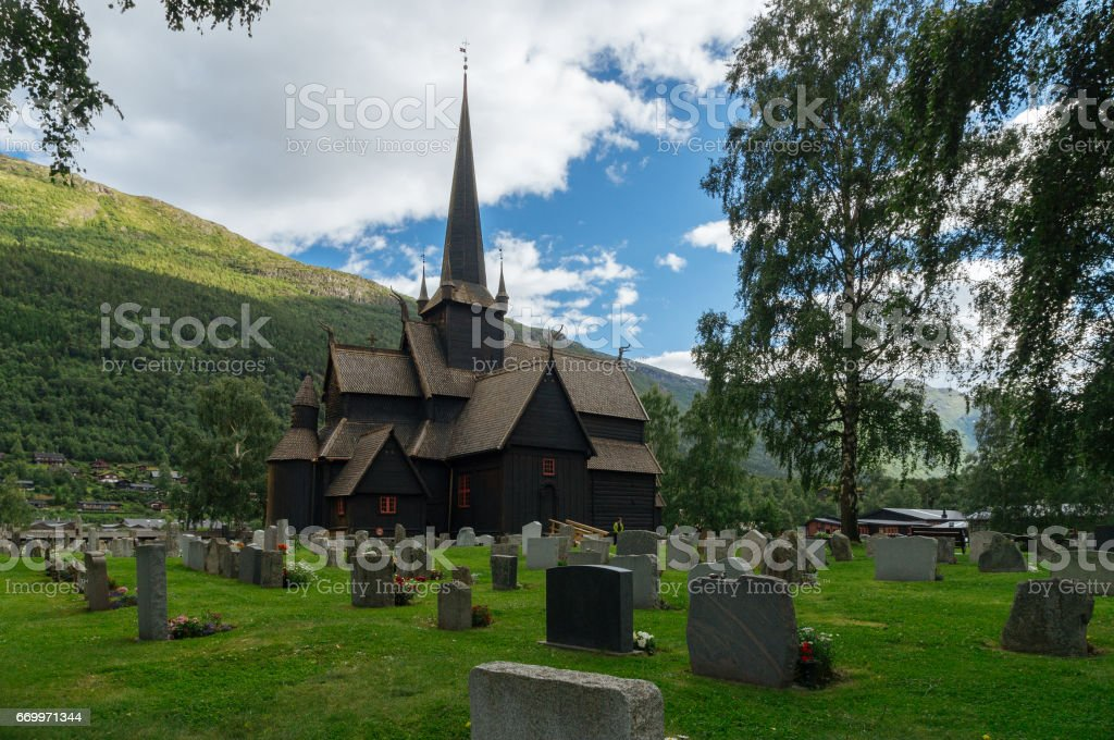 Old wooden stave chapel surrounded by cemetery stock photo