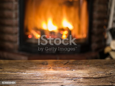 istock Old wooden table and fireplace with warm fire. 626958484