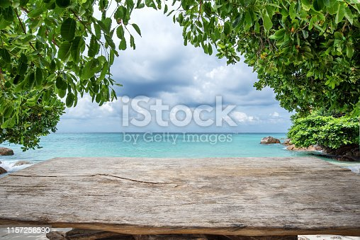 Old wooden table and tropical beach background