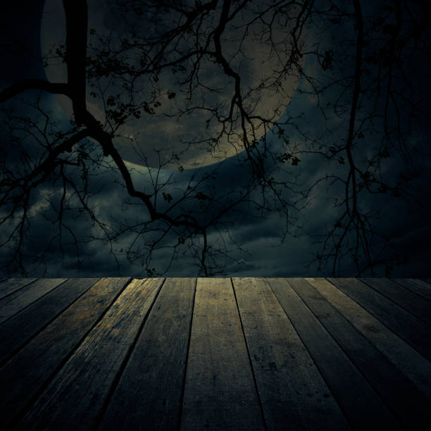 Old wooden table over dead tree, Halloween background stock photo