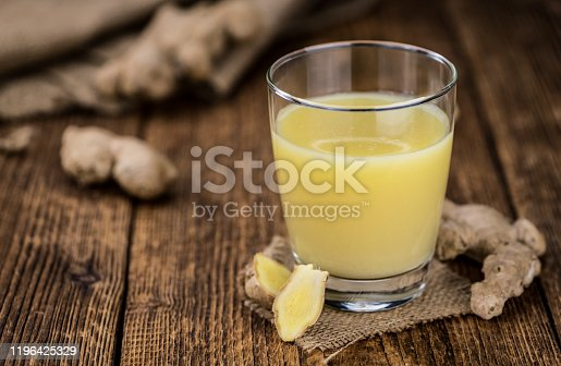 Healthy Ginger Sap on a wooden table as detailed close-up shot (selective focus)