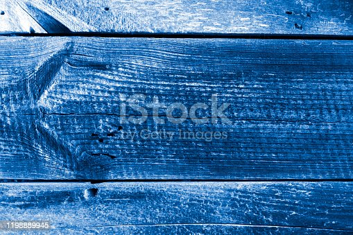 istock Old wooden unpainted board background. Textured background toned in Classic Blue color. 1198889945