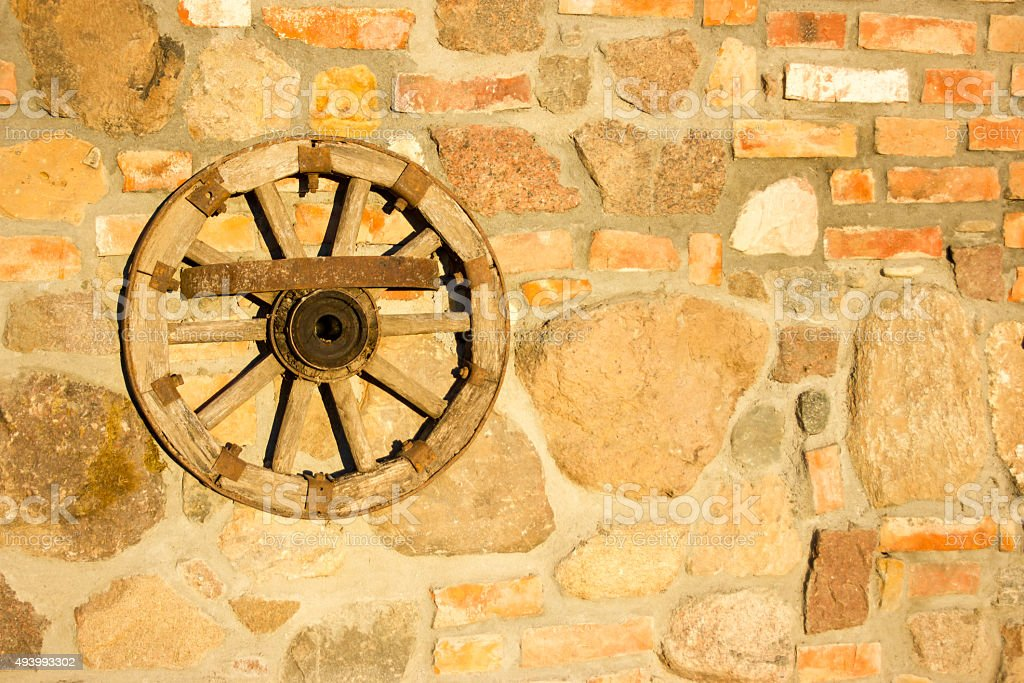 Old wooden wheel hanging on the wall. stock photo