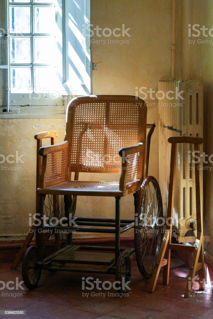 Old wooden wheelchair in the interior. stock photo