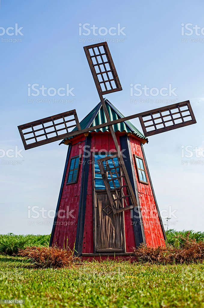 Old wooden windmill painted in red, with blue sky stock photo