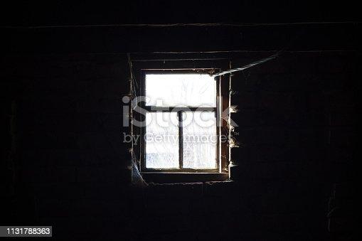 Old wooden window in dark. Sunlight outside, darkness inside