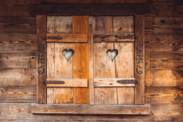 Old wooden windows of a wooden house with two cutouts of hearts stock photo