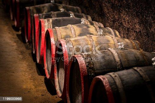 Old wooden wine barrels shot in closeup in a wine cellar.