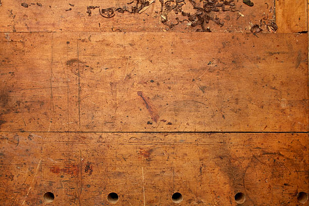 Old Woodworking Bench Top Background Old woodworking bench top background. Stained and marked form years of use.  workbench stock pictures, royalty-free photos & images