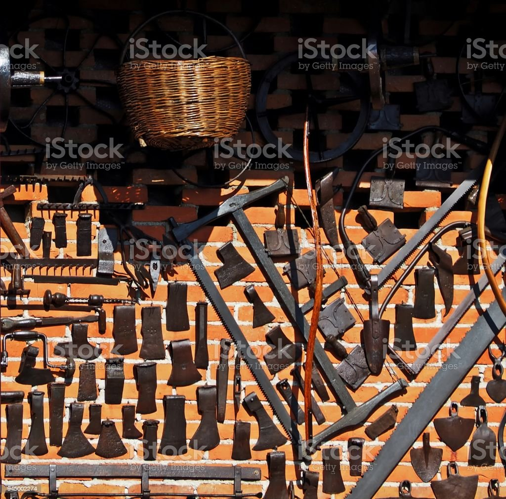 Old Woodworking Tools And Agricultural Tools Hung On A Brick Wall