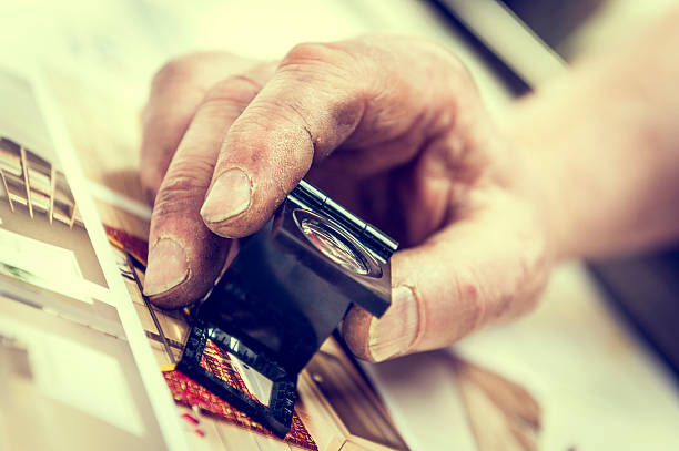 Old Worker Dirty Hand Controlling a Print Through Magnifying Lens stock photo