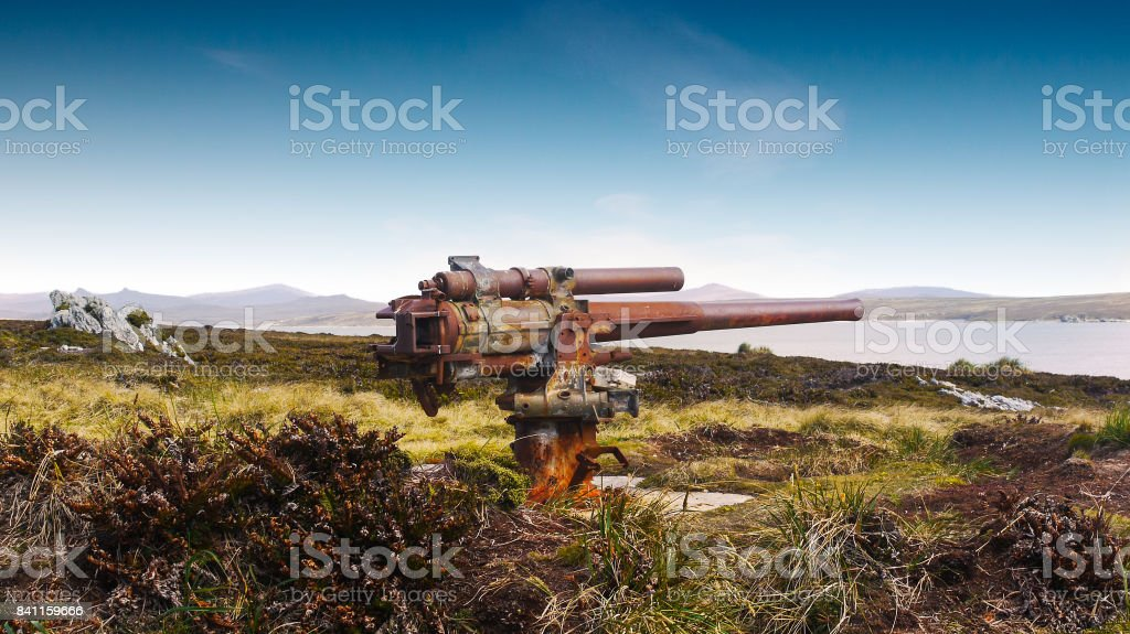 Old world war 2 mounted naval gun at Ordnance Point, entrance to Stanley Harbour, Falklands Islands. Also a land mine area from Falklands War. stock photo