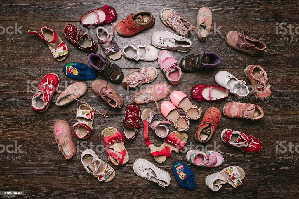 Old worn baby (child) shoes on the floor. flat lay stock photo