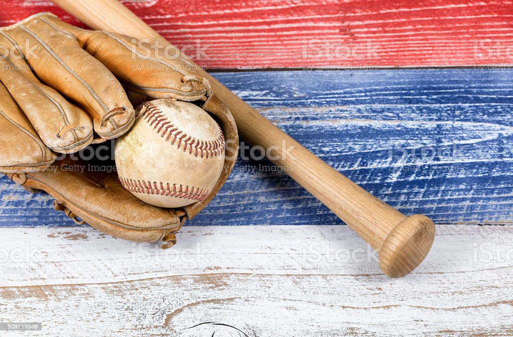 Old worn baseball equipment on faded boards painted in American stock photo