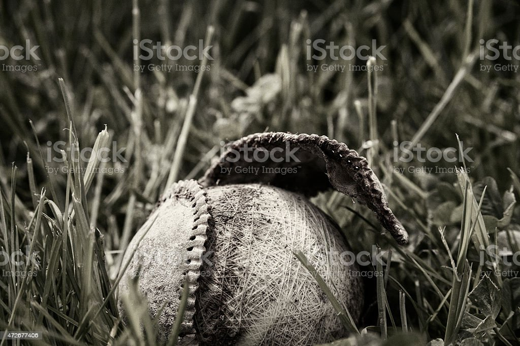 Old worn baseball in tall grass with cover coming off stock photo
