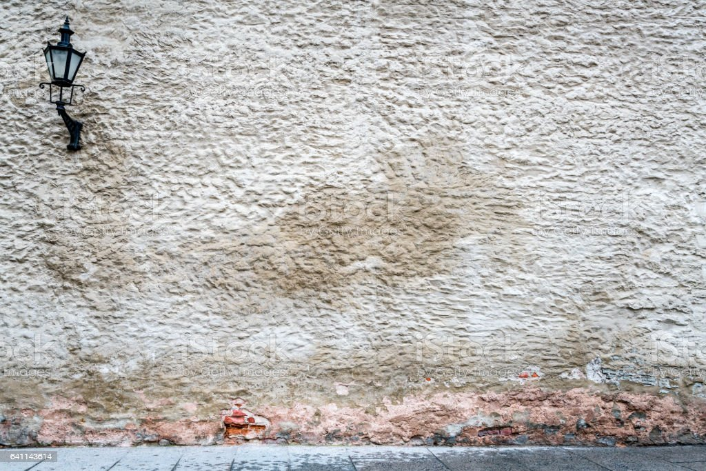 Old worn exterior wall with heavy texture, stone and plastered bricks. Old black vintage street lamp on the wall. royalty-free stock photo