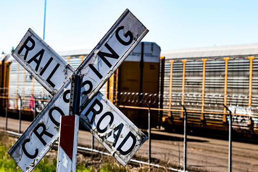 Old worn railroad crossing sign in front of a barbed wire fence and cars in the day