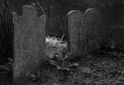 Old, worn tombstones in the corner of the cemetery.