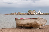 An old worn, rusty, weathered boat is lying on the sandy beach of the Greek Island of Chios in the Aegean Sea on a morning in spring. In the background (somewhat blurred) is small white painted church (or chapel) on a small rocky islet dedicated to Agios Isidoros (St. Isidore)