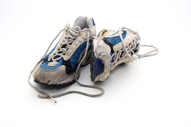 old wornout trainers - running shoes stockfoto's en -beelden
