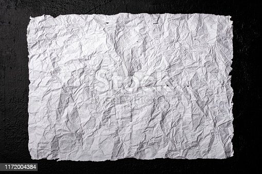 891131294istockphoto Old, wrinkled paper on a black background. 1172004384