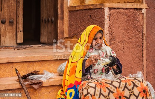 Old Wrinkled Woman in Traditional Clothing Sitting on the Street of Ancient Village of Abyaneh in Iran