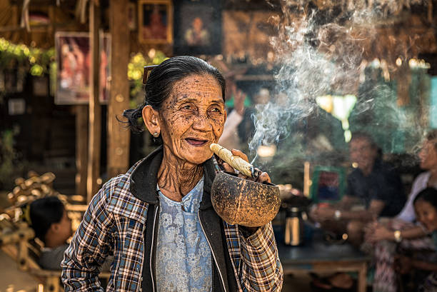 Old wrinkled woman smoking  a big cheroot cigar stock photo