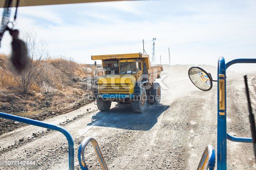 istock Old yellow dump truck moving in a mine. View from another truck 1077142444
