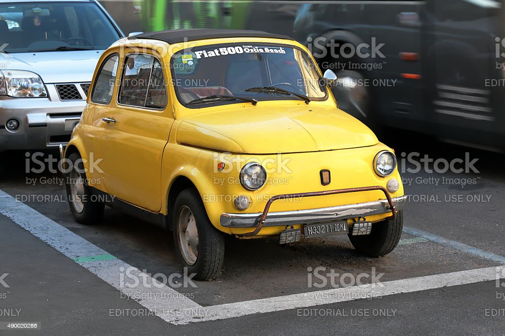Old yellow Fiat 500 parked on street in Rome, Italy. stock photo