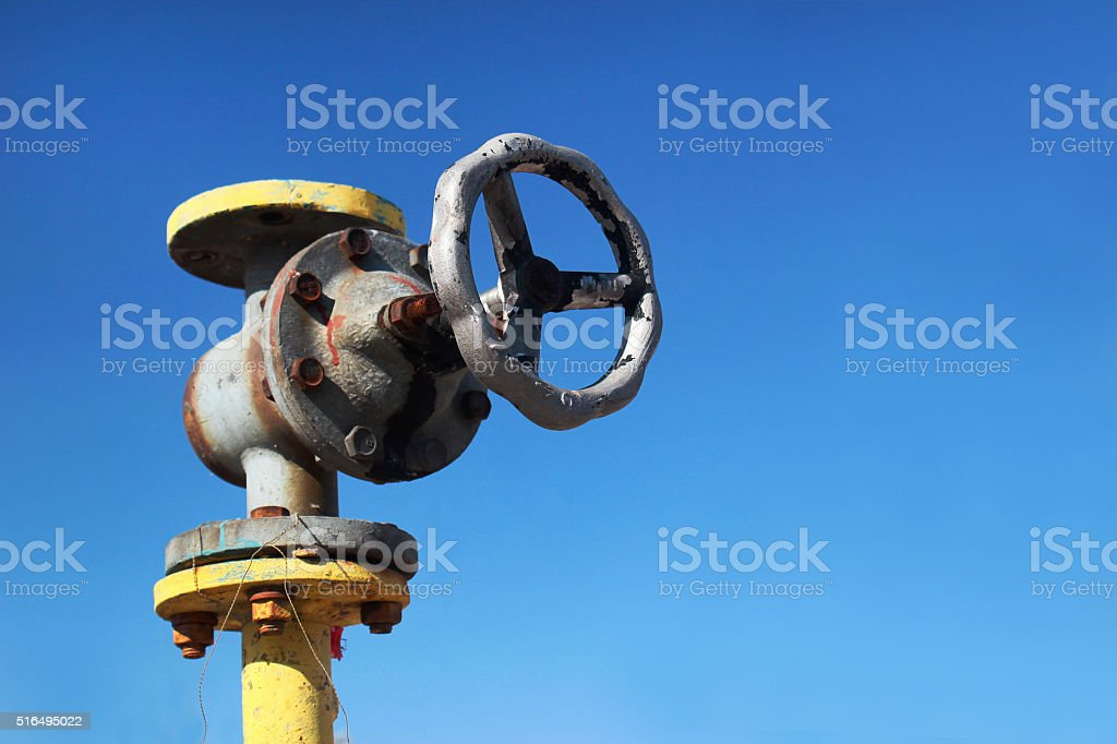 Old yellow gas pipe with valve on blue sky background stock photo