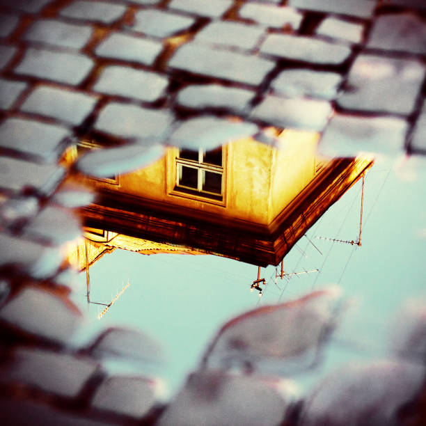 Old yellow house in reflection of puddle on pavement. European vintage city view. Cozy street stock photo
