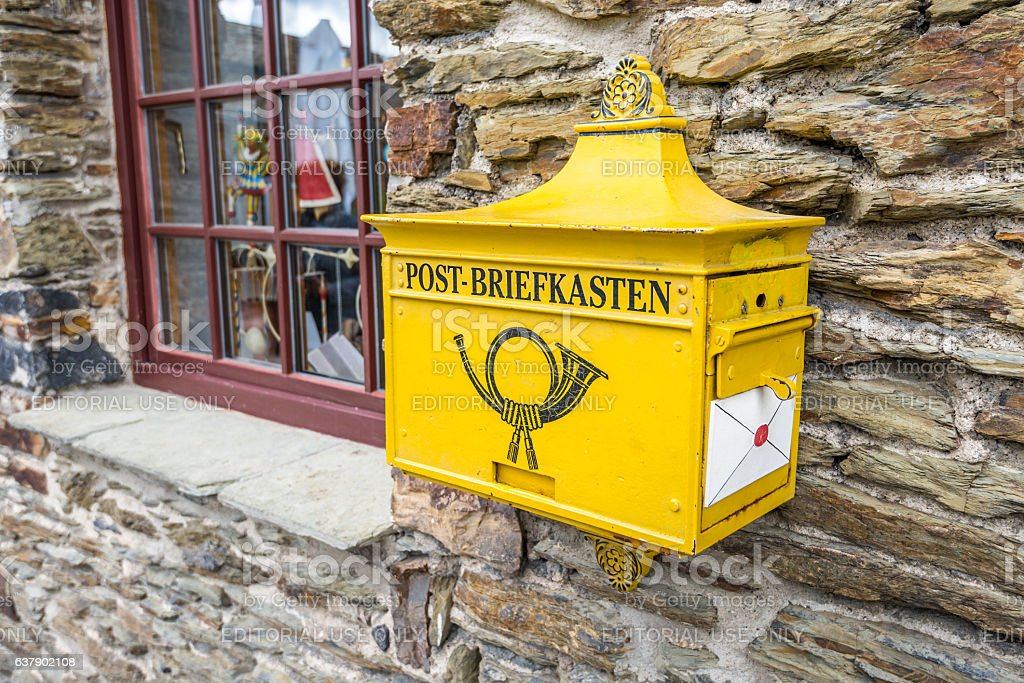 Old yellow post mailbox in Germany stock photo