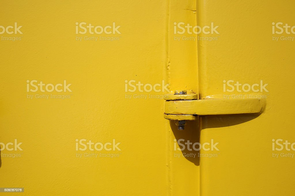 Old yellow ships door and bolt close up as background stock photo