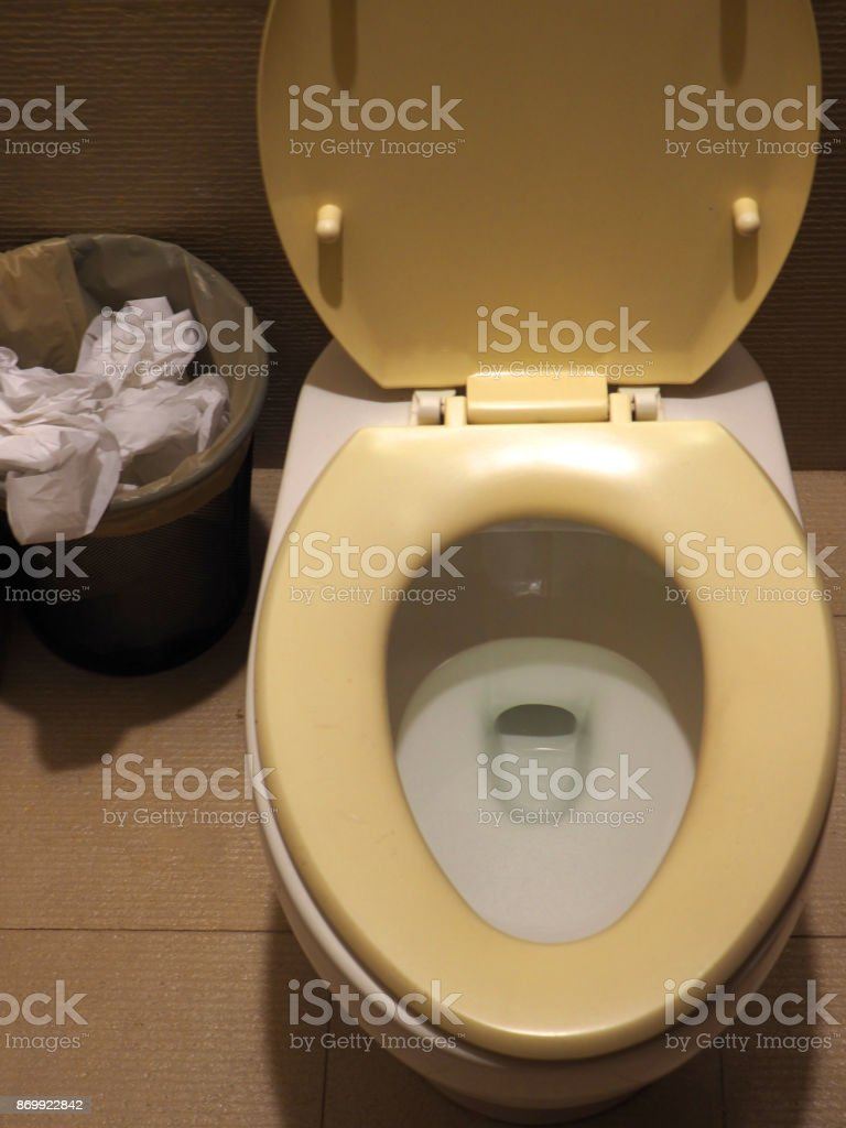 Old yellow stained toilet seat with rubbish bin full of tissue paper, vertical top view stock photo