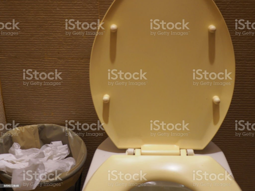 Old yellow stained toilet seat with rubbish bin full of tissue paper, front view stock photo
