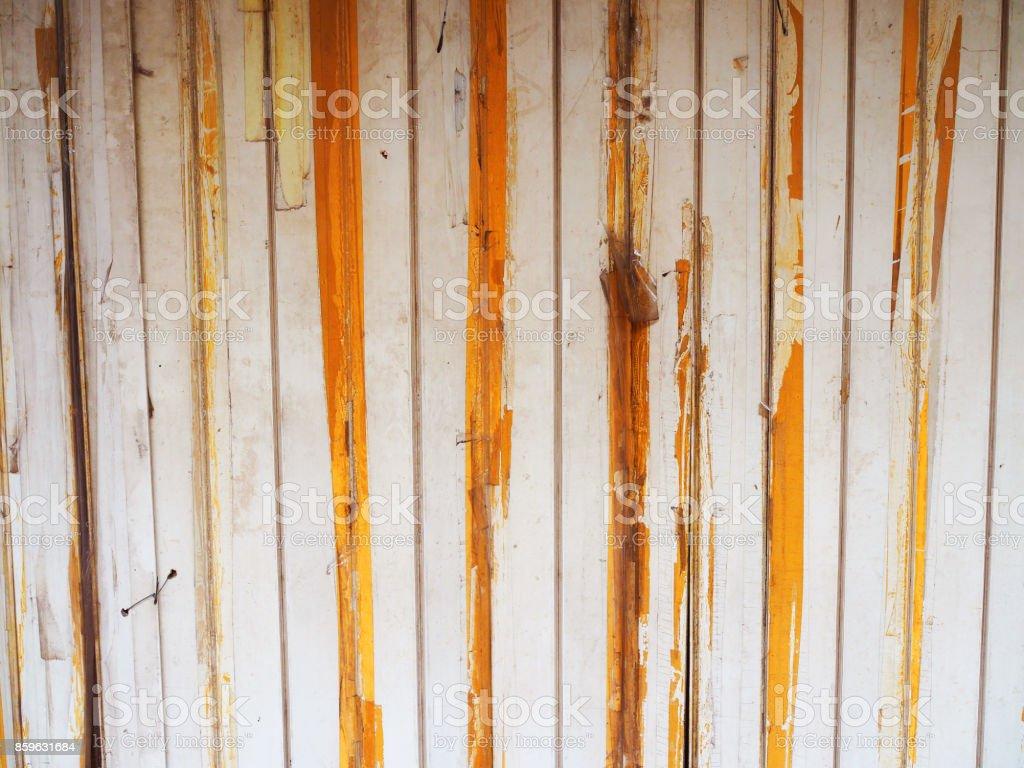 Old yellow stained white folding sliding shutter door stock photo