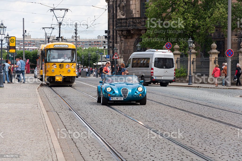 Old yellow tram and luxury retro style car in Dresde stock photo