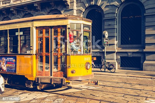 Milan: old yellow tram of the public transport company of the city of Milan circulating in the paved streets